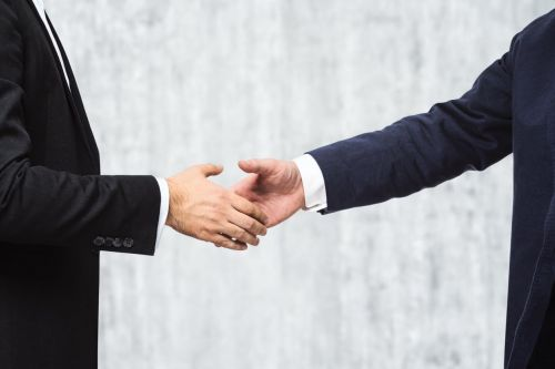 Two businessmen shake hands insider trading concept